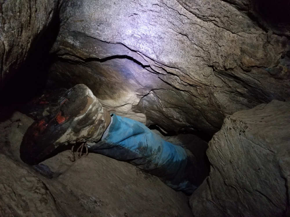 Photo of foot and lower leg disappearing into a cave